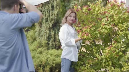 oturum : Young positive girl in white shirt and jeans posing near the berry bush for the young man with camera outdoors. Male photographer taking photos of attractive woman in the summer park