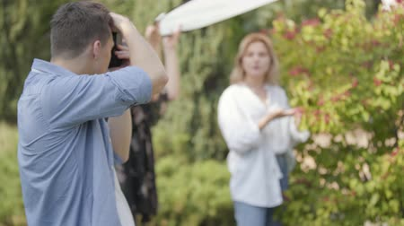 oturum : Young positive girl in white shirt and jeans posing near the berry bush for the young man with camera outdoors. Male photographer taking photos of woman in the park. Focus on the photographer