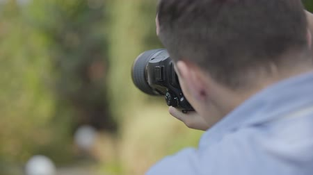 photoshoot : Professional photographer taking photos while standing outdoor. Stock Footage