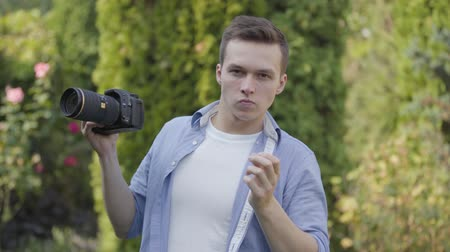 oturum : Portrait of young professional male photographer taking photo with camera standing outdoors. Photography, profession, photo session