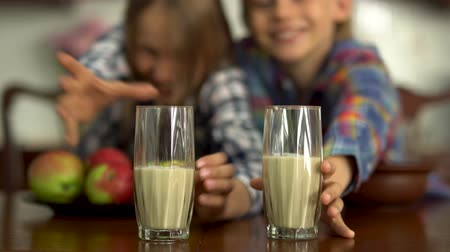 piada : Hand of the mother pouring milk in the glasses for the kids in the foreground. Boy and girl grabbing and drinking milk in the background. Healthy lifestyle, happy loving family Stock Footage