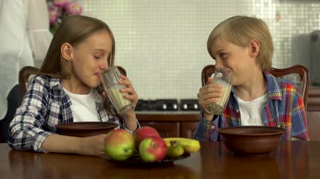 blague : The boy and girl drinking milk from transparent glasses. Siblings enjoy their healthy beverage sitting in the modern kitchen at the table. Healthy lifestyle, happy family Vidéos Libres De Droits
