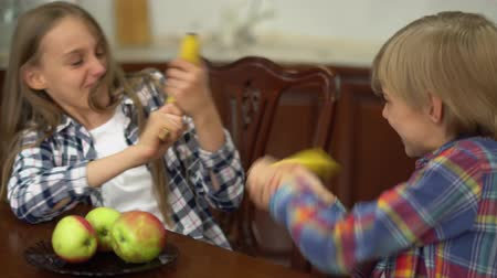 fool : Two cute children fighting with each other jokingly using bananas like a weapon in the kitchen. Boy and girl spending time together at home. Healthy lifestyle. Carefree childhood