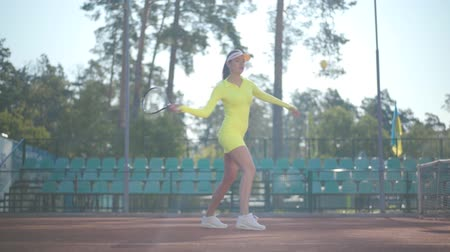 служить : Confident pretty girl in a sportswear holds a tennis racket while standing on the tennis court oudddoors. Young tennis player playing a sports match on sunny summer day Стоковые видеозаписи
