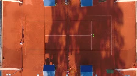 служить : Top view of two tennis players playing tennis on the outdoors tennis court. A man and a woman in sportswear are playing a sports match on a sunny summer day.