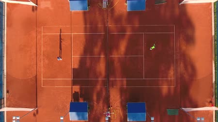 teniszütő : Top view of two tennis players playing tennis on the outdoors tennis court. A man and a woman in sportswear are playing a sports match on a sunny summer day.