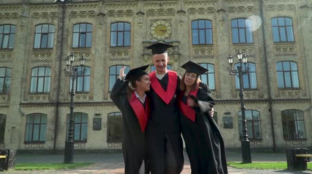 диплом : Three happy joyful students in black and red mantles celebrating their graduation in front of university building. Two girls and one boy hugging while walking. Graduation, new life. Slow motion Стоковые видеозаписи