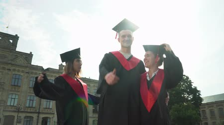 polegar : Three happy joyful students in black and red mantles celebrating their graduation in front of university building. Two girls and one boy showing thumb up. Graduation, new life