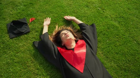 学士 : Portrait of happy smiling girl in black and red mantle laying on the grass enjoying her freedom. Young woman celebrating her graduation. New life concept 動画素材