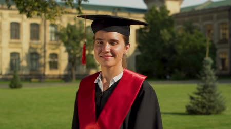 completo : Portrait of confident cute girl in black mantle and cap standing in front of university building looking at camera. Young woman celebrating her graduation Stock Footage