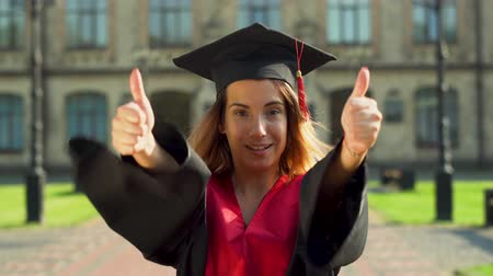 diploma : Portrait of confident cute girl in black mantle and cap standing in front of university building looking at camera. Young woman celebrating her graduation Stockvideo