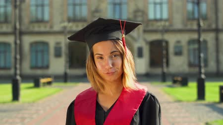 master's degree : Portrait of confident cute girl in black mantle and cap standing in front of university building looking at camera. Young woman celebrating her graduation Stock Footage