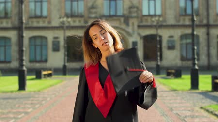 plášť : Portrait of confident girl in black and red mantle holding cap standing in front of the university building. Young woman celebrating her graduation Dostupné videozáznamy