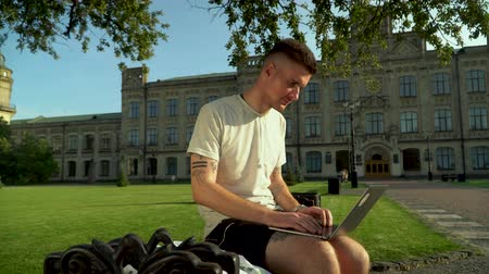 netbook : Young busy man working at his laptop sitting on the bench in front of large beautiful building. The student searching for information using his gadget at the university. Summertime Stock Footage