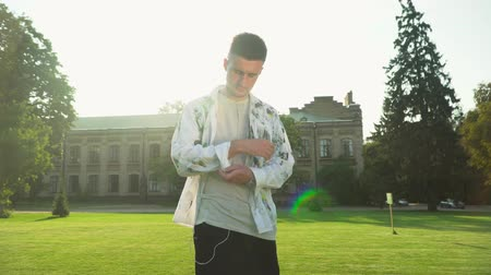 выражающий : Portrait of a young serious man rolling up his sleeves outdoors. The student at the university. Sun shining brightly. Education concept. Summertime leisure. Slow motion