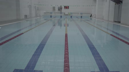 trabalhar fora : Athletic professional swimmer hardly working out in indoor empty pool jumping and swimming across track