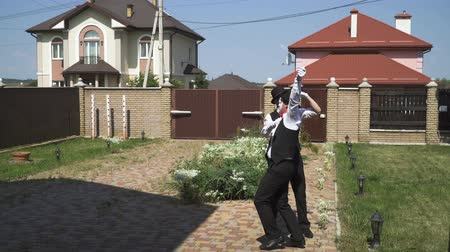 divadelní : Two funny male mimes with white faces in white and black clothes doing performance in front of large house. Actors pulling invisible rope, making funny gestures