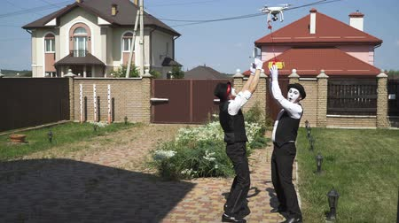 acteur : Two funny mimes with white faces in white and black clothes doing performance in front of large house. Actors taking a small present from the drone. Gift concept, happiness