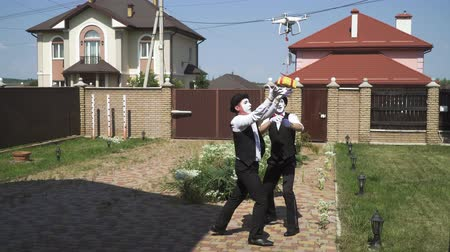 piada : Two funny mimes with white faces in white and black clothes doing performance in front of large house. Actors taking a small present from the drone. Gift concept, happiness