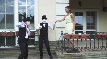 acteur : Two funny mimes with white faces in white and black clothes doing performance in front of large house. Actors inviting the girl to help them with their show