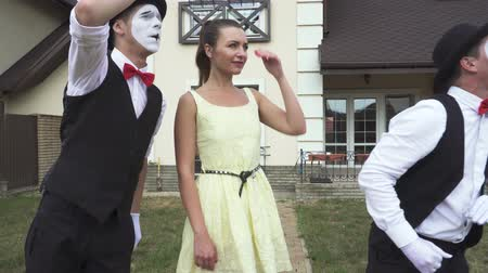 acteur : Two funny male mimes with white faces in white and black clothes doing performance with the young girl in front of large house. Actors making show outdoors Stockvideo