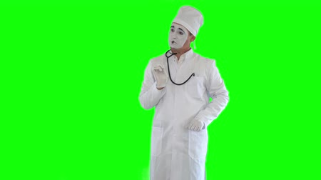 kaszel : Funny male mime in the white gown with stethoscope imitating work of the doctor. One actor making show on green background. Chromakey Wideo