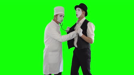 acteur : Funny male mime in white gown with stethoscope imitating work of the doctor. The patient and doctor performing show. Two actors making the show on green background. Chromakey