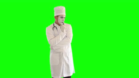 yüz buruşturma : Funny male mime in the white gown with stethoscope imitating work of the doctor. One actor making show on green background. Chromakey Stok Video