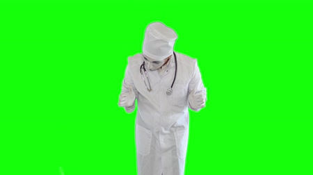 cisza : Funny male mime in the white gown with stethoscope imitating work of the doctor. One actor making show on green background. Chromakey Wideo