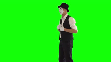 acteur : Funny male mime with white face in white and black clothes imitating suffering of sick person. One male actor performing show on green background. Chromakey