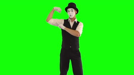 yüz buruşturma : Funny male mime with white face in white and black clothes imitating bodybuilder. One male actor performing show on green background. Chromakey
