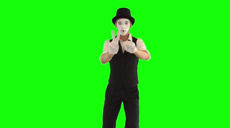 acteur : Funny male mime with white face in white and black clothes imitating magician. One male actor performing show on green background. Chromakey
