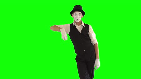 acteur : Funny male mime with white face in white and black clothes imitating relaxation. One male actor performing show on green background. Chromakey