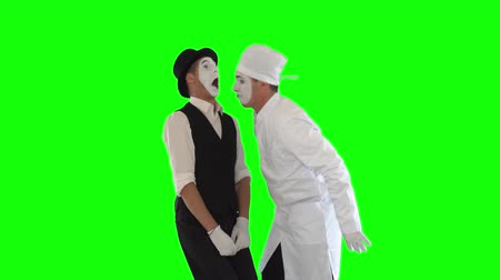 acteur : Funny male mime in white gown and hat imitating work of evil dentist. The patient afraids of the doctor. Two actors making show on green background. Chromakey