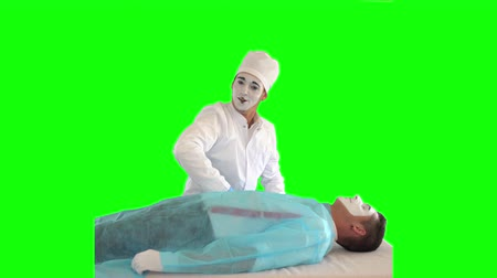 acteur : Funny male mime in white gown and hat imitating work of the doctor. The guy imitating surgeon operation. The patient and doctor performing show. Two actors making the show on green background. Chromakey