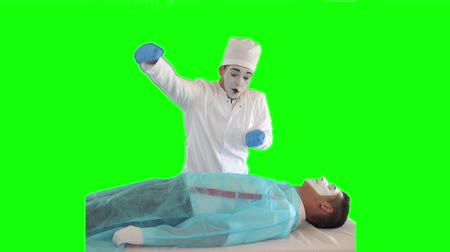 acteur : Funny male mime in white gown and hat imitating work of the doctor. The guy imitating resuscitation. The patient and doctor performing show. Two actors making the show on green background. Chromakey