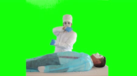 acteur : Funny mime in white robe and hat imitating work of the doctor. The guy imitating surgeon operation. The patient and doctor performing show. Two actors making show on green background. Chromakey