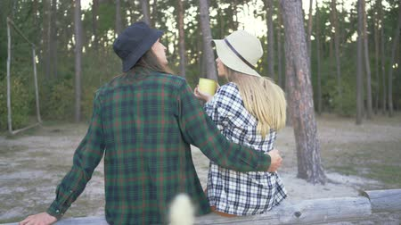 tela escocesa : Back view of tourist couple in plaid hipster shirts and hats sitting in the forest. Young caucasian girl is drinking tea or coffee from the yellow cup resting next to her boyfriend. Archivo de Video