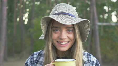 pléd : Young happy caucasian girl in plaid shirt and hat drinking tea or coffe from the yellow cup, smiling to camera and winking.
