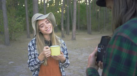 gadjet : Young pretty caucasian woman posing with a yellow cup on the background of forest. Boyfriend taking pictures of his lovely girl on vacations. Stock Footage