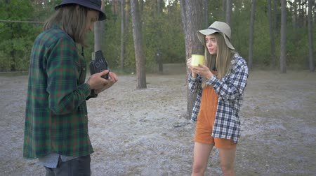gadjet : Young guy making video on Small tiny camera of posing pretty hipster girl with cup of tea or coffee on the background of forest Stock Footage