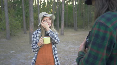 gadjet : Young caucasian woman in straw hat posing with a yellow cup on the background of forest. Boyfriend taking pictures of his lovely girl on vacations.