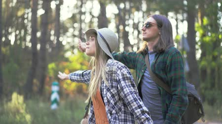 pléd : Hipster millennial tourist happy couple in plaid hipster shirts want to catch car making hitch-hiking near forest