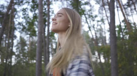 humor : Portrait of cheerful beautiful girl in plaid shirt and hipster outfit smiling and spinning around herself on the background of beautiful forest. Slow motion