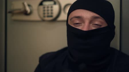 balaclava : Close-up of young caucasian thief in black clothes and balaclava looking at camera. The guy stealing things from safe. Concept of crime, criminal, offense against the law