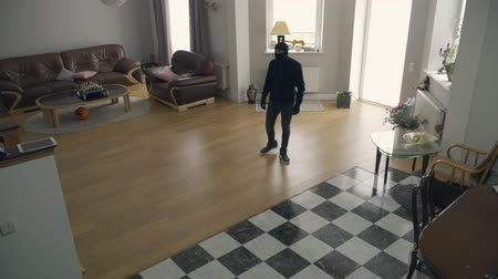 přestupek : The thief in black clothes and balaclava walking in large living room. The guy stealing money. Concept of crime, criminal, offense against the law. Top view Dostupné videozáznamy