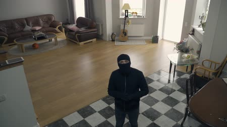 soymak : The thief in black clothes and balaclava walking in the large living room. Caucasian man raising hands noticing security camera. Concept of crime, criminal, offense against the law. Top view
