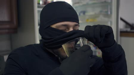 přestupek : Close-up of young caucasian thief in black clothes raising his balaclava and drinking from the glass. The guy stealing things in rich house. Concept of offense against the law