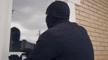 włamywacz : Close-up of the thief in black clothes and balaclava breaking into the rich house through the window. Concept of offense against the law, crime, robbery, burglary. Back view