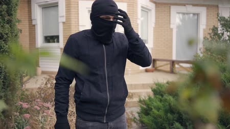 přestupek : Portrait of young caucasian thief in black clothes putting on balaclava before breaking into house. The guy going to steal things in the rich house. Concept of offense against the law, robbery, burglary